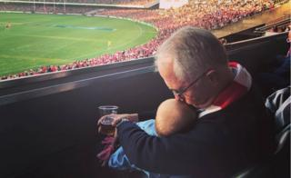 Malcolm Turnbull kisses his young granddaughter while holding her in one hand and a beer in another, at a sporting match in Sydney on Saturday
