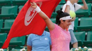 Ons Jabeur portant un drapeau tunisien