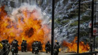 Una explosión en la zona de Altamira, en Caracas, mientras varios policías pasan por allí en motocicletas.