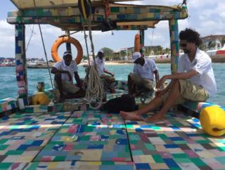 People sit on board the Flip-flop Dhow