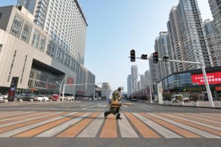 A worker with sanitising equipment crosses the road in front of a hospital in Yichang city of Hubei
