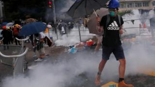 A protester reacts to a tear gas during a demonstration against a proposed extradition bill in Hong Kong, China June 12, 2019
