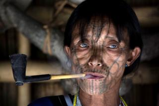 in_pictures A tattooed woman smokes a pipe