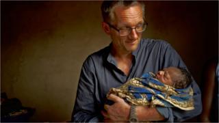 Michael Mosley holding newborn baby