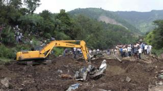 Heavy machinery removes debris as rescue personnel search for survivors and bodies of victims after a landslide along a highway at Kotrupi