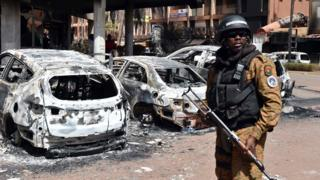 Burkina Faso official stands guard next to burnt cars outside hotel attacked in Ouagadougou