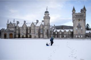 in_pictures Geraint Stone pulls his two-year-old son Arthur on his sledge across the snow-covered lawn in front of Balmoral Castle, Royal Deeside