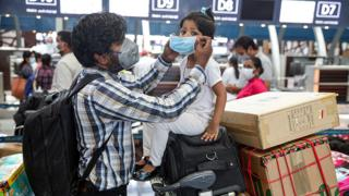 A man puts a mask on the face of a young girl as they wait at Muscat International Airport with other Indian nationals for a repatriation flight - 12 May 2020