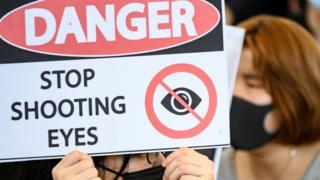 香港國際機場一號客運大樓內一名女示威者舉起「危險,停止射擊眼睛」標語(13/8/2019)