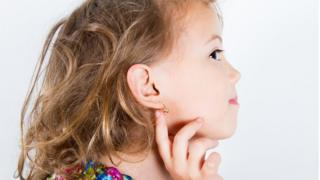 Child with pierced ear showing off her earring