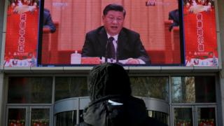 """man stands and watches a large screen during President Xi Jinping""""s speech at a grand gathering to celebrate the 40th anniversary of China""""s reform and opening-up in Beijing on December 18, 2018 in Harbin, China"""