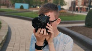 Callum Utley taking a photo with a digital SLR camera