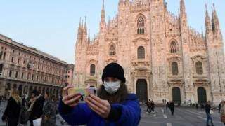 A tourist in a protective mask takes a selfie in the Piazza del Duomo, Milan