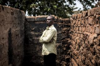 Emmanuel stands in front of the remains of his house.