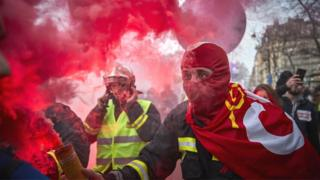 A fireman holds a flare aloft during a protest against pension reform plans in Paris, 10 December 2019