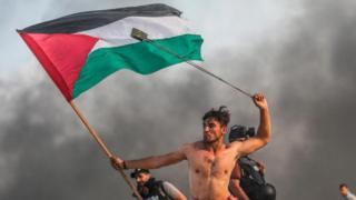 Warga Palestina melempari batu dan membakar ban sebagai tanggapan terhadap pasukan Israel selama demonstrasi maritim di Kota Gaza pada 22 Oktober 2018