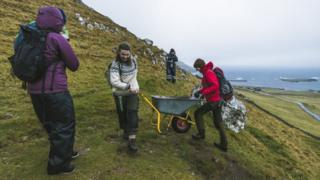 Brown Group members help each other to push a wheelbarrow in the hills in Kirkjubøur