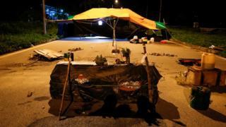 Hình ảnh quan tài đặt ngay lối vào cổng công ty dệt Pacific Crystal hồi tháng 7. Phía sau là căn lều người dân dựng lên để phản đối.