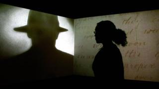 жінка дивиться на силует чоловіка в капелюсі