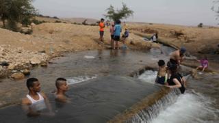 נערים פלסטינים ומתנחלים יהודים מתאספים בנקודת מים ליד הכפר הכבוש אל-אג'ה הכבושה בעמק הירדן ב -15 במאי 2020, כאשר האזור מוביל לגל חום
