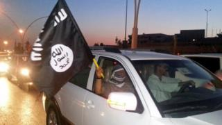 IS fighter waves a flag of the group in the city of Mosul, Iraq on 23 June