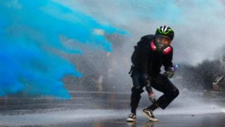 An anti-government protester is sprayed with blue-coloured water in Hong Kong - 15 September 2019