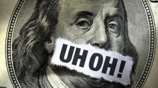 Billete de dólar con palabras UH OH! escritas.