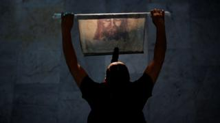A woman holds a cloth with an image of Jesus Christ during the Good Friday at Brasilia Cathedral