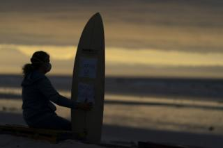 A woman stands with a surfboard on the beach in the twilight.