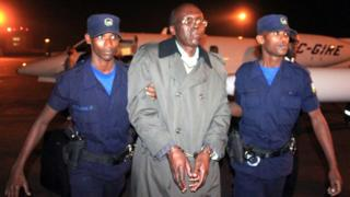 Leon Mugesera (C) is escorted handcuffed by policemen to a police vehicle on the tarmac as he arrives at Kigali International Airport late on January 24, 2012
