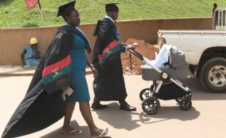 Graduates push a stroller and walk in a campus after the 68th graduation ceremony, where more than 14 000 students received degrees, at Makerere University in Kampala, Uganda, on January 19, 2018