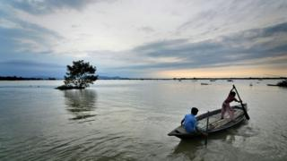 Youngster paddle through a landscape inundated by water in the flood affected Morigaon district of Assam state, India, 01 September 2015.