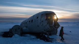 A woman observes the remains of the Sólheimasandur air disaster in southern Iceland