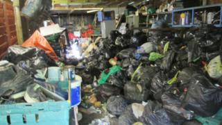 Black bin bags of rubbish piled up in a garage