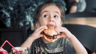 بچهای در حال خوردن همبرگر