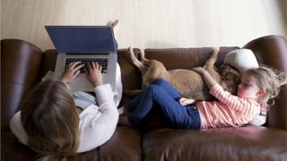 Woman on computer while daughter and dog sleep on couch beside her