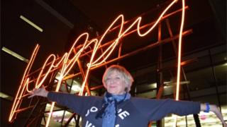 Victoria Wood in front of a neon sign saying 'happy'