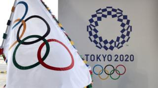 An Olympic Flag pictured next to the Tokyo 2020 logo