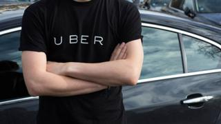 A man wearing an Uber t-shirt and standing in front of a car