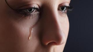 Una toma muy cerrada del rostro de una mujer que llora