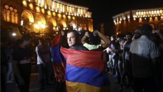 Мужчина на митинге в Ереване держит армянский флаг