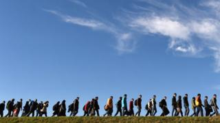 Migrants walk to a first registration point of the German federal police after they crossed the Austrian-German border in 2015