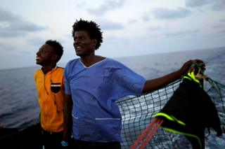 Esam (left), 22, and Ahmed, 38, both from Sudan, stand on board NGO Proactiva Open Arms rescue boat in central Mediterranean Sea