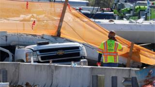 A worker stands near a truck beneath a collapsed pedestrian bridge at Florida International University in Miami, Florida, U.S., March 16, 2018.