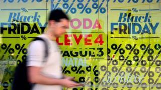 Homem passa em frente à vitrine com cartazes da Black Friday