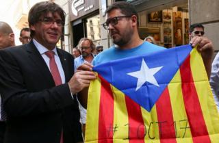 Katalonya Bölgesi hükümerinin lideri Carles Puigdemont (solda), bağımsızlık yanlısı bir vatandaşla kameralara poz veriyor