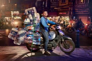 A man posed on his motorcycle with lots of large water containers stacked on top of each other