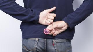 A man holding a condom behind his back