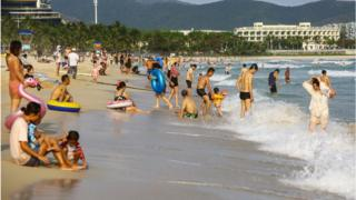 People enjoying the beach in Sanya in China's southern Hainan province.