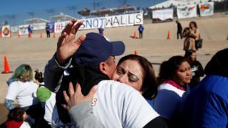 Familiares abrazándose en la frontera de Estados Unidos y México.